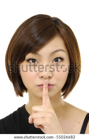 close up of young asian man holding finger to her lips - stock photo