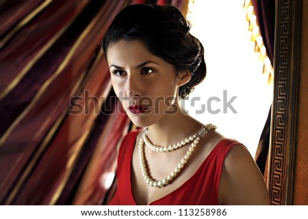 close-up of young beautiful woman in red dress against drapery - stock photo