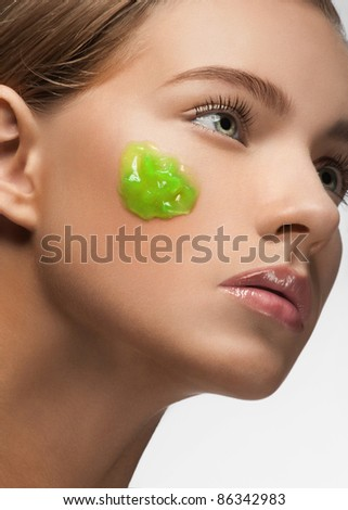 Close-up of young beautiful woman with green moisturizing facial mask on her face - stock photo