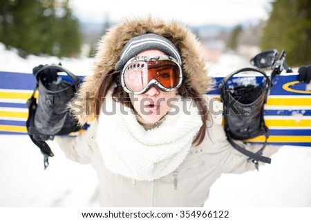 Close up of young beautiful woman with ski mask holding her snowboard at ski slope Young woman  in ski resort holding snowboard on her shoulders and smiling.Concept of winter holiday  - stock photo