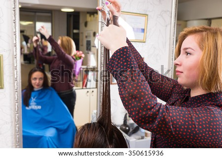 Close Up of Young Blond Stylist Trimming Long Hair of Brunette Client Seated in Chair in Salon with Blurred Reflection in Background Mirror