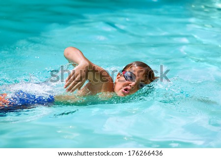 Close up of young boy at swimming practice outdoors. - stock photo