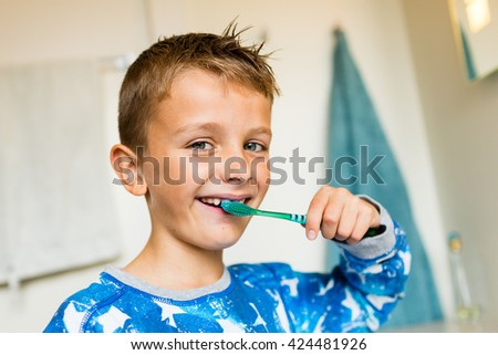Close-up of young boy brushing his teeth with toothbrush while standing in bathroom with natural daylight. - stock photo