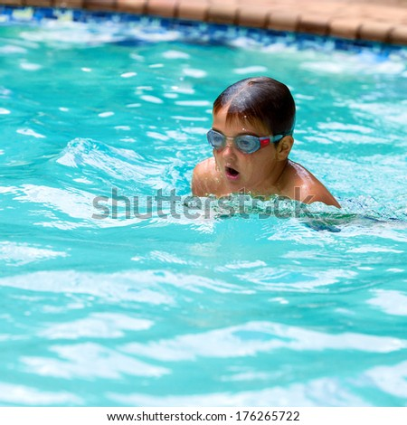 Close up of young boy swimming in outdoor pool. - stock photo