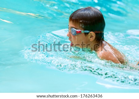 Close up of young boy swimming in pool. - stock photo