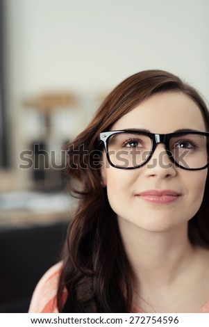 Close Up of Young Brunette Woman Wearing Eyeglasses with Black Frames Looking Up Optimistically, Daydreaming, or Thinking of Something Inspirational - stock photo