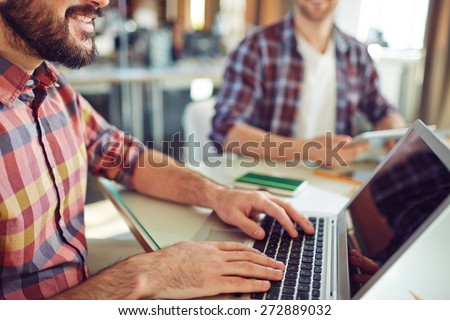 Close-up of young businessman computing in office - stock photo