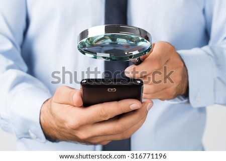 Close up of young businessman searching, spying the mobile, smart phone - stock photo