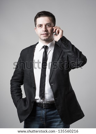 Close up of young businessman using smart phone on gray background