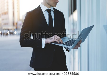 Close-up of young businessman wearing black suit using modern laptop or computer outdoors  - stock photo