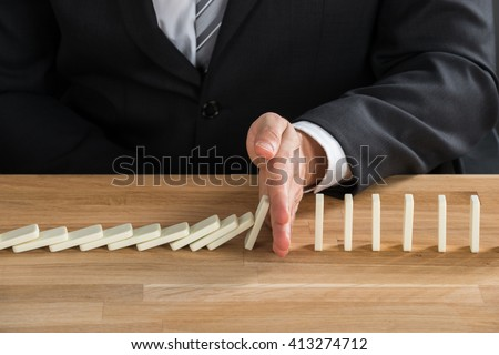 Close-up Of Young Businessperson Stopping Dominos From Falling On Wooden Desk