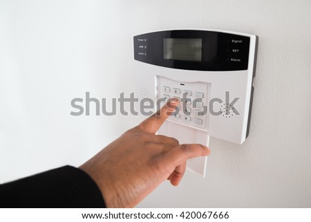 Close-up Of Young Businesswoman Hand Entering Code In Security System - stock photo