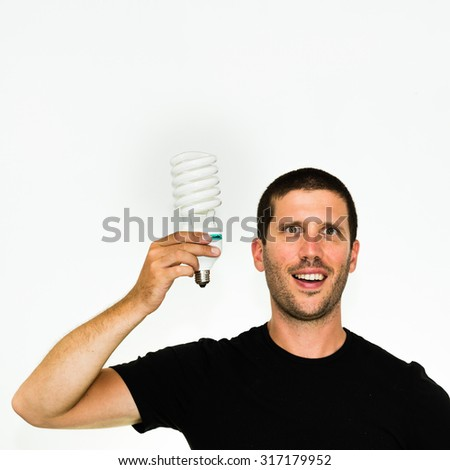 close-up of young caucasian man having a brilliant idea holding an energy save bulb in his hand - conceptual image isolated on white background