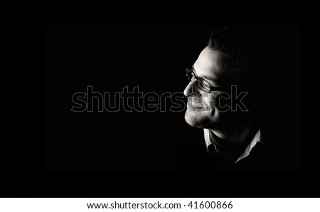 Close-up of young confident and happy man, low key, black and white - stock photo