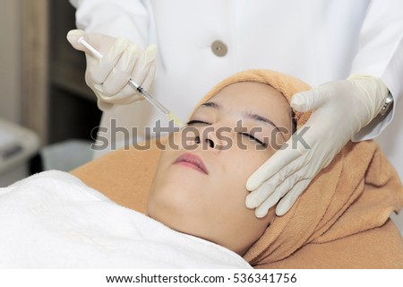 Close up of young cosmetologist injecting botox in female face. The woman is closed her eyes at spa