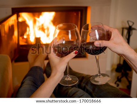 close up of young couple drinking wine in front of an open wood fire.  - stock photo