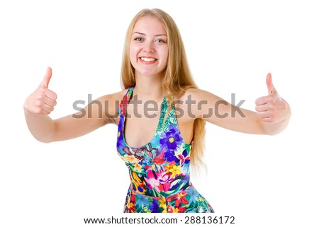 Close-up of young cute smile girl teenager shows thumbs up and looking in camera in mix color summer dress posing isolated on white background, positive human emotion, facial expression - stock photo