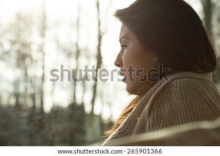 Close-up of young depressed crying woman sitting alone - stock photo