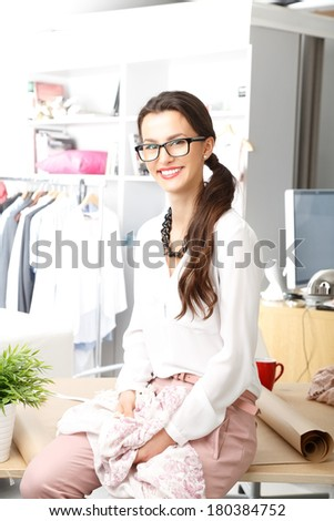 Close-up of young fashion designer working in her studio.