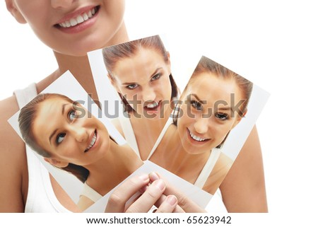 Close-up of young female holding three images of herself - stock photo