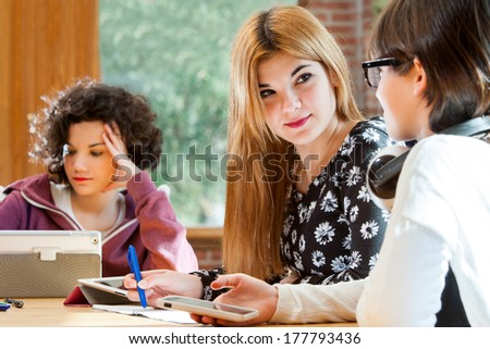 Close up of young female students discussing schoolwork at desk indoors. - stock photo