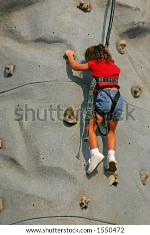 Close-up of young girl climbing a rock wall