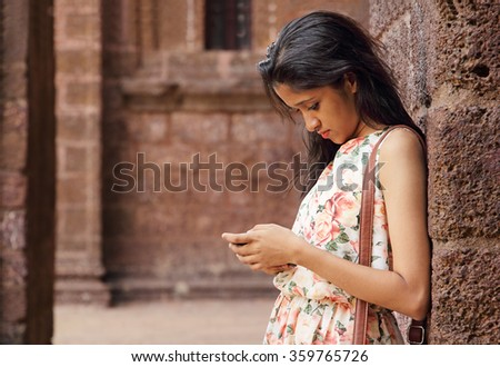 Close up of young girl working seriously on smart phone, leaning against red brick wall - stock photo