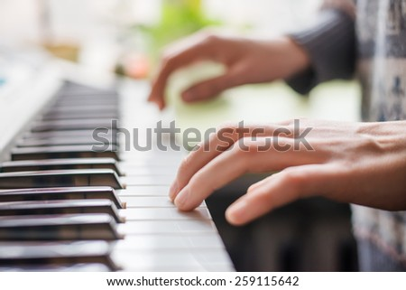 Close up of young girls hands, playing the keys - stock photo