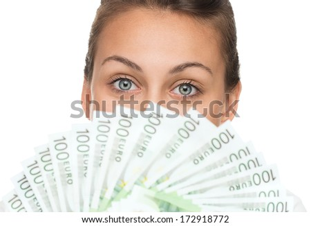 Close up of young happy woman holding pile of money isolated on white background - stock photo