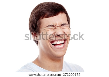 Close up of young hispanic man laughing out loud with closed eyes - laughter is best medicine concept - stock photo