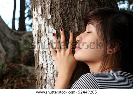 close up of young lady hugging a tree - stock photo