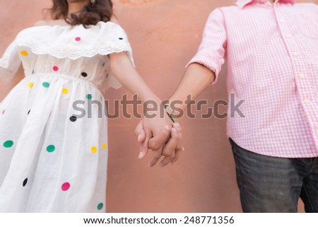 Close up of young lovers couple holding hands - stock photo