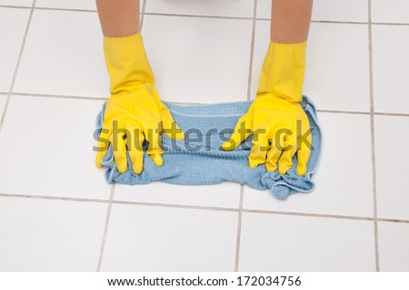 Close-up Of Young Maid Wearing Gloves Cleaning Floor - stock photo
