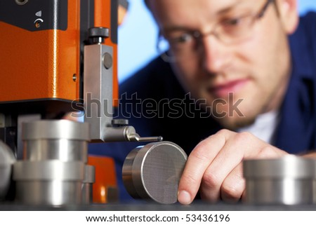 Close-up of young male engineer in blue overall taking precision measurement of metal parts with micrometer, isolated on blue background. - stock photo