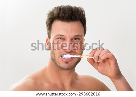 Close-up Of Young Man Brushing His Teeth With Tooth Brush