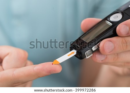 Close-up Of Young Man Hand Using Glucometer To Check Blood Sugar Level - stock photo