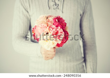 close up of young man holding bouquet of flowers. - stock photo