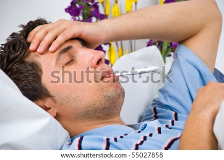 Close up of young man lying down in bed taking temperature and having flu - stock photo