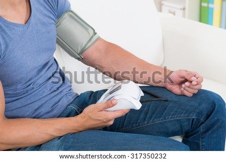 Close-up Of Young Man Measuring His Blood Pressure At Home - stock photo