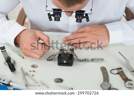 Close-up Of Young Man Repairing Wrist Watch At Desk In Workshop - stock photo