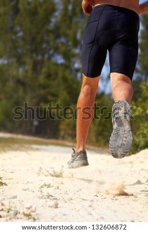 Close-up of young man running in sand, rear view