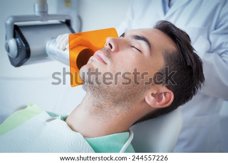Close up of young man undergoing dental checkup in the dentists chair - stock photo