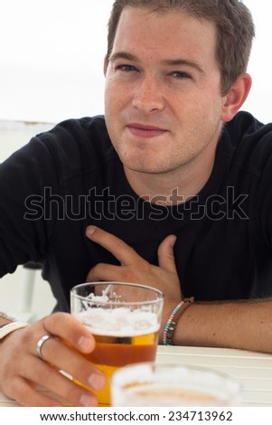 Close up of young man with glass of beer. - stock photo