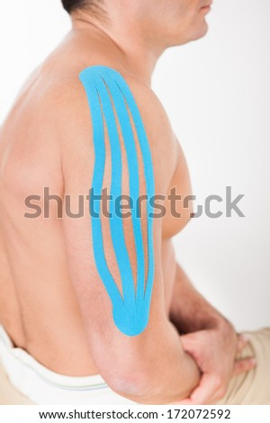 Close-up Of Young Man With Kinesio Tape Applied On Shoulder - stock photo