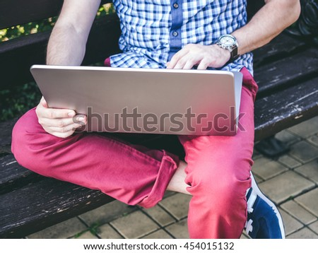 Close up of Young Man working on his laptop sitting on the bench in park - stock photo