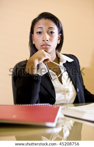 Close-up of young  mixed-race Hispanic African-American woman studying with books on table - stock photo
