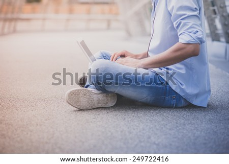 close up of young model handsome blonde man with notebook and headphones in the city - stock photo