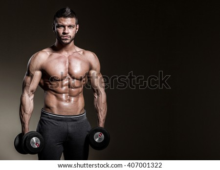 Close up of young muscular man with dumbbells on a black background - stock photo
