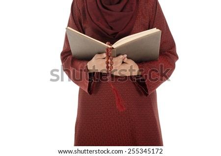 Close up of young muslim woman read Quran with tasbih in the Ramadan time. - stock photo