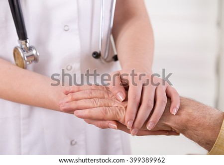Close up of young nurse holding old man's hands and comforting him. Senior care concept - stock photo